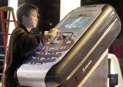 A technician works on an oversized-model of a mobile phone at the LG booth at the Consumer Electronics Show in Las Vegas, Nevada January 4, 2006. The show, which runs from January 5 through January 8, is the world's largest trade show for consumer technology and is expected to draw 2,500 exhibitors and 130,000 attendees from more than 110 countries. REUTERS/Steve Marcus
